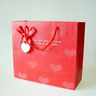 绸带手提,传统风格红色花形装饰,正面滴胶彩箔粉装饰.